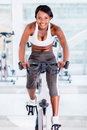 Fit woman doing spinning at the gym and smiling Stock Photos