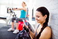 Fit woman in gym holding smart phone, brick wall Royalty Free Stock Photo