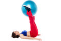 Fit woman holding exercise ball between legs gym lying on the floor with raised a swiss Stock Photography