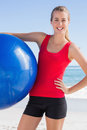 Fit woman holding exercise ball smiling at camera on the beach Royalty Free Stock Photos