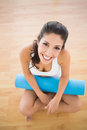 Fit woman holding her exercise mat sitting and smiling at camera on parquet floor home Royalty Free Stock Image