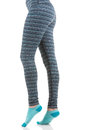 Fit woman legs wearing colourful striped trousers and blue socks from side view in standing on toes position Royalty Free Stock Photo