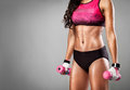 Fit woman lifting dumbbells torso of a young on a grey background Stock Photos