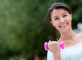 Fit woman lifting weights exercising at the park Stock Image