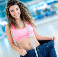 Fit woman loosing weight in big pants after a lot of Stock Photo
