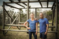 Fit woman and man standing against monkey bars during obstacle course Royalty Free Stock Photo
