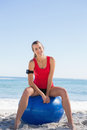 Fit woman sitting on exercise ball smiling at camera the beach Royalty Free Stock Image