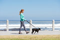 Fit woman smiling and walking dog on path by sea Royalty Free Stock Photo