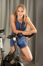 Fit woman spin bicycle jim beautiful young in sports outfit standing next to a in a Stock Photos