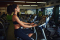 Fit woman in a spin class at gym attractive girl with afro hair spinning on simulator bicycle equipment fitness center Stock Photography