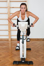 Fit woman on stationary bicycle in gym Royalty Free Stock Photography