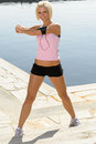 Fit woman stretch body by water pier Royalty Free Stock Images