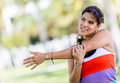 Fit woman stretching arm her arms outdoors before exercising Royalty Free Stock Image