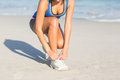 Fit woman tying her shoelace at the beach Stock Photography