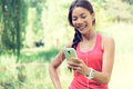 Fit woman using cell phone while listening music happy young to on smartphone smiling mixed race asian caucasian female is in Stock Photo