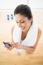 Fit woman using smartphone taking a break from workout at home in bright room Stock Photos