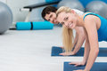 Fit young couple working out at the gym doing press ups on their mats and turning to smile camera with an attractive blond Royalty Free Stock Image
