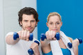 Fit young couple working out at the gym with dumbbells standing holding them extended towards camera Stock Photos