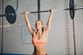 Fit young female athlete lifting heavy weights beautiful strong woman with barbell and weight plates overhead caucasian Royalty Free Stock Image