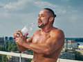 Fit young man bottle drinking water muscle shaped outdoor relaxed with energy drink Royalty Free Stock Photos