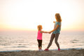 Fit young mother and daughter on the beach, looking out to sea Royalty Free Stock Photo