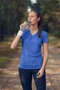 Fit young woman drinking bottled water slender in sportswear as she pauses on a forest track to re hydrate during a training run Stock Image