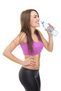 Fit young woman drinking water during workout spontaneous candid shot of caucasian brunette smiling looking sideways wearing pink Stock Photo