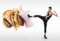 Fit young woman fighting off fast food on gray background Royalty Free Stock Photography