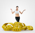 Fit young woman with a large measuring tape on gray background Royalty Free Stock Images
