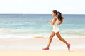 Fit young woman running along a tropical beach the edge of the surf on sunny in her sportswear with her long hair fenake runner Stock Image