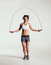 Fit young woman skipping rope portrait of muscular exercising with jumping on grey white background Stock Photos
