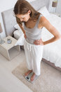 Fit young woman standing on scale in bedroom full length of a at home Royalty Free Stock Image