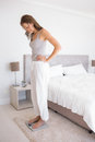 Fit young woman standing on scale in bedroom full length side view of a at home Royalty Free Stock Photo