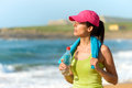 Fitnes woman after exercising fitness beautiful holding water bottle and sweating on summer hot day in beach female athlete work Royalty Free Stock Images