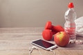 Fitness background with bottle of water, apple and smartphone Royalty Free Stock Photo
