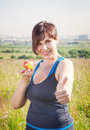 Fitness beautiful plus size woman with apple showing thumbs up outdoor Royalty Free Stock Photos
