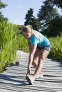 Fitness blond girl stretching down her legs and back, outdoors Royalty Free Stock Photo