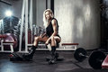 Fitness blonde woman posing on bench in the gym Royalty Free Stock Photo