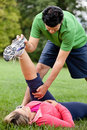 Fitness coach stretching woman's leg Royalty Free Stock Images