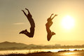 Fitness couple jumping happy at sunset with the sun in the background Stock Photo