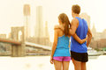 Fitness couple relaxing after running in new york brooklyn city usa happy sporty fit young interracial enjoying view of Royalty Free Stock Images