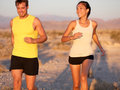 Fitness couple running jogging outside laughing sport happy training together outdoors runners in cross country run on trail Stock Photos