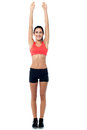 Fitness enthusiast stretching her arms young trainer exercising white background Royalty Free Stock Photography