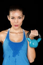Fitness exercise crossfit woman holding kettlebell strength training biceps beautiful sweaty fitness instructor looking intense Stock Photo