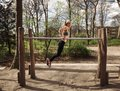 Fitness female doing parallel bar dips side view of muscular young woman triceps on bars at park caucasian model exercising Stock Photography