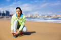 Fitness female runner at city beach woman getting ready for running challenge in gijon asturias spain lacing sport shoes before Stock Photos