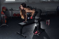 Fitness girl execute exercise with dumbbells, on broadest muscle of back. Royalty Free Stock Photo
