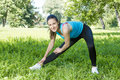 Fitness girl outdoor doing stretching exercise looking at camera Stock Photography