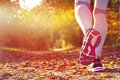 Fitness girl running at sunset in city center Stock Images