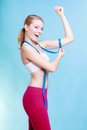 Fitness girl sporty woman measuring her biseps on blue Royalty Free Stock Photo